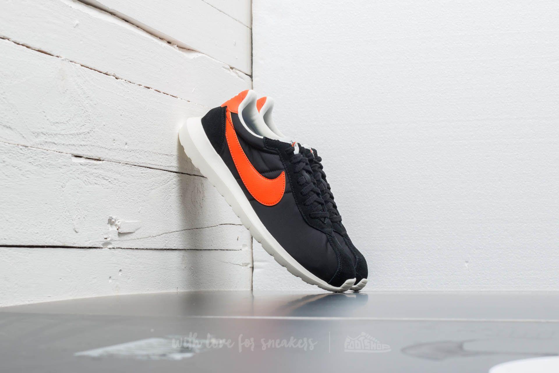 black nike shoes with orange swoosh